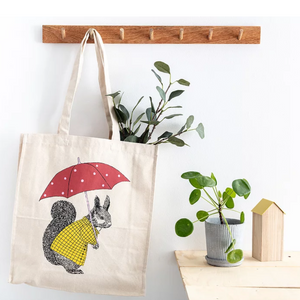 A tote bag with squirrel illustration hangs from a wooden coat hook, there is a wooden top table with potted plant and ornament on the right of the image.