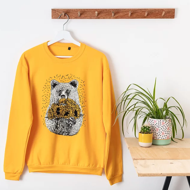 A bright yellow jumper with a bear holding sunflowers. The jumper is on a hanger which hangers from a wooden coat hook against a white wall. There is a table on the left of the image with some potted plants on it.