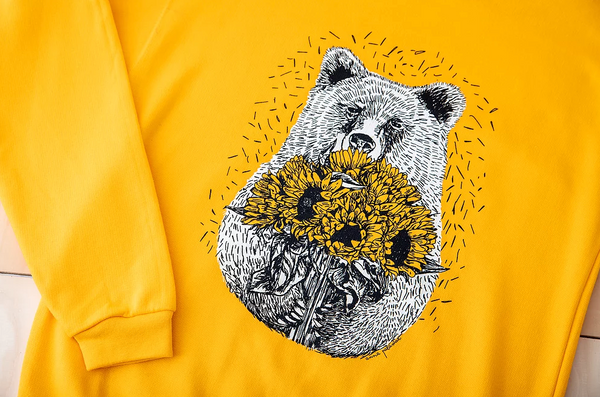 Close up of a bright yellow jumper with a bear holding sunflowers.