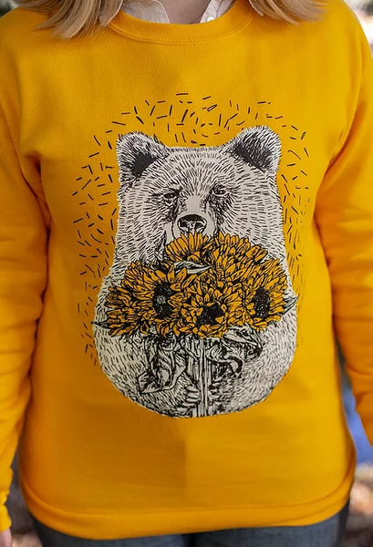 Image shows the torso and arms of a model wearing a yellow jumper with illustration of a bear holding sunflowers.