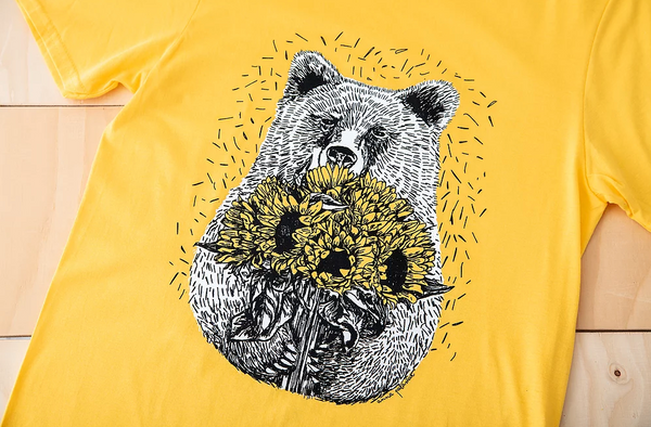 Close up of a bright yellow tshirt with an illustration of a bear holding sunflowers.