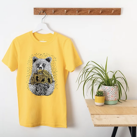 A bright yellow tshirt with an illustration of a bear holding sunflowers. The t shirt is on a hanger which is hanging on from a wooden coat hook against a white wall. There is a wooden top table on the left with some potted plants on it.