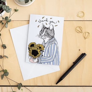 Card with illustration of a cat in pajamas holding sunflowers with the saying ' thank you'. The card is on a white envelope on a wooden table top with a black pen, paper clips and a plant.