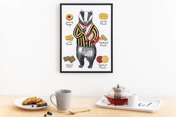 Print in black frame hanging above a shelf with tea tray, mug and plant of biscuits.  The illustration is of a badger in suit and bowtie holding biscuits surrounded by smaller illustrations of different types of biscuits.