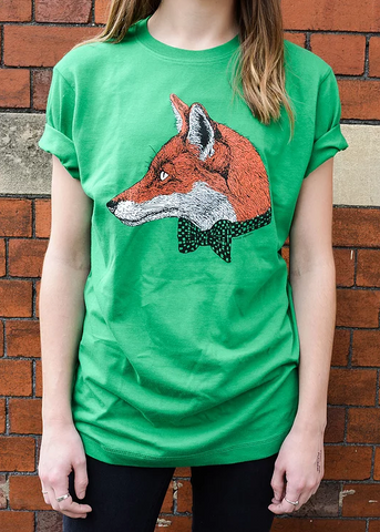 Image shows torso and arms of a model wearing a green t shirt with fox head and bow tie illustration. There is a brick wall in the background.