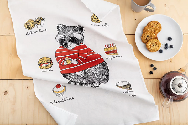 A white tea towel with a raccoon and cake illustration lays on a wooden table top alongside a teapot, mug and plate of cookie.