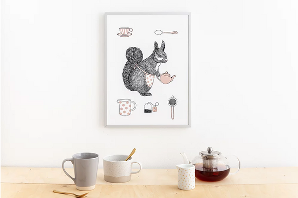 Print in a white frame hanging on a white wall above a wooden table top with a teapot, mugs, spoons and milk jug. The illustration is of a squirrel wearing an apron and holding a teapot. There are smaller illustrations above and below her of teacup, spoon, milk jug, teabag and strainer.