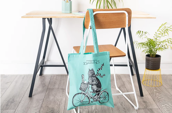 A bright yellow tote bag with an illustration of a cat riding a bicycle. The bag is hanging on the back of a chair at a desk with a potted plant on the left.