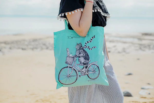 Image shows a model using the 'pascal the cat' tote bag, there is an out of focus beach scene in the background.