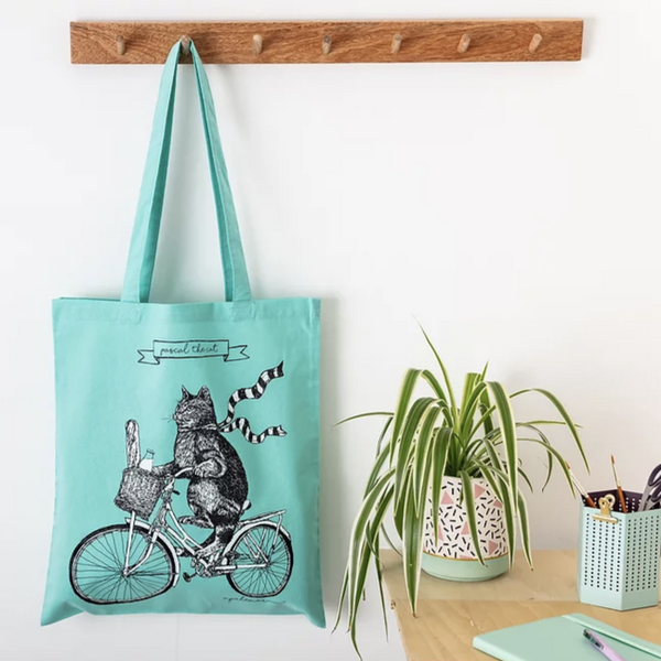 A bright yellow tote bag with an illustration of a cat wearing a scarf and riding a bicycle.. The bag is hanging on a wooden coat hook against a white wall. There is a table on the left of the image with some potted plants and stationary on it.