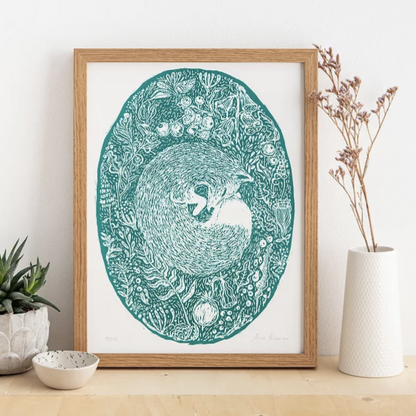 Green woodland fox print in wooden frame sitting on shelf with other ornaments.