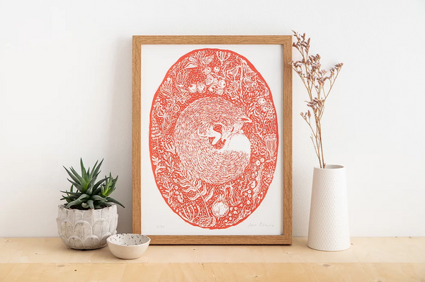 Red woodland fox print in a wooden frame sitting on a shelf with pot plant, vase and ceramic dish.