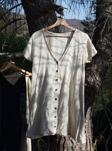 A bone coloured button dress hangs from a wooden hanger outside on a tree.