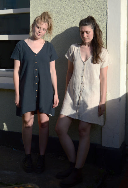 Two white women lean against a light green wall, there is a window visible in the background. One model has blonde hair and wears a slate coloured button dress, her head is tilted and she is looking at the camera. The model on the right has brown hair, wears a bone coloured button dress and is looking down. They are both wearing dark ankle boots.