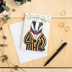 Card with illustration of a badger in a suit and bowtie holding champagne, text on the top reads ' champagne for everyone' with confetti around it. The card is on a white envelope on a wooden table top with a black pen, paper clips and a plant.