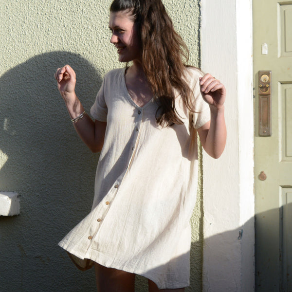 A white woman with long brown hair wears a bone coloured button dress. She is in front of a light green wall and door and is spinning so there is movement in the dress.