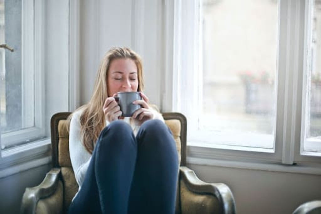 woman-relaxing-with-cup-of-tea-listening-to-music
