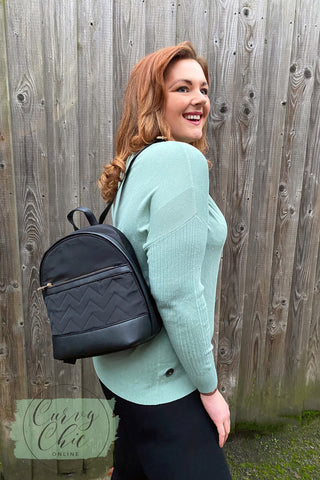 sage jumper with black quilted backpack