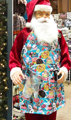 Santa wearing Two Lumps of Sugar Yummy Cakes apron and silli mitts and hotties