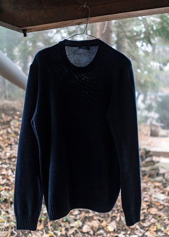 Navy blue cashmere pullover hanging outside to refresh.