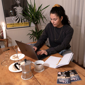 Woman in a dark grey seamless merino pullover working on a laptop at a wooden desk.