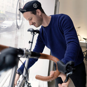 Man in a bike shop wearing a blue organic cotton pullover.