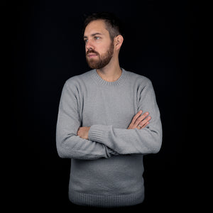 Man wearing a grey organic cotton pullover in front of black background.