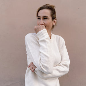Woman wearing white organic cotton pullover in front of beige wall.