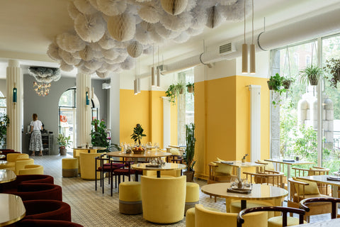 Plants in a well lit, modern, yellow and white restaurant