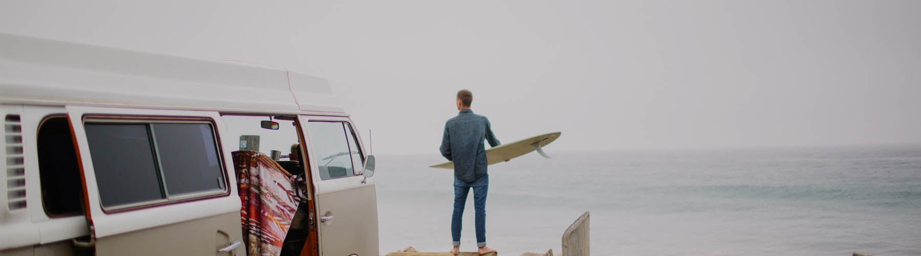Guy looking out at sea holding a surfboard