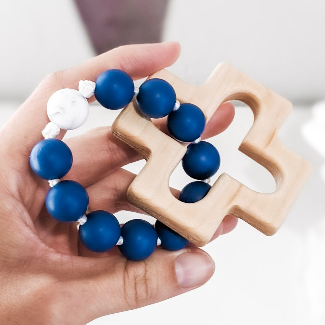 Hand holding blue and white teething rosary ring