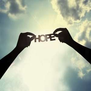 Hands holding the word hope up to the clouds