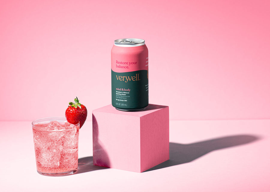 Beauty shot of glass garnished with strawberry beside Truss Veryvell Mind & Body CBD sparkling water.