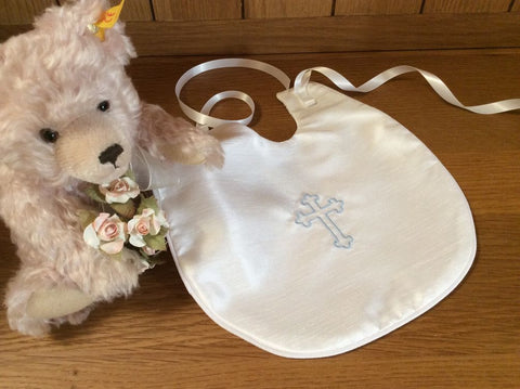 Christening bib with an embroidered cross.