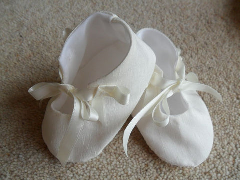 Plain christening bootees with a bow.