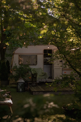 A small camper partially obscured by shade trees