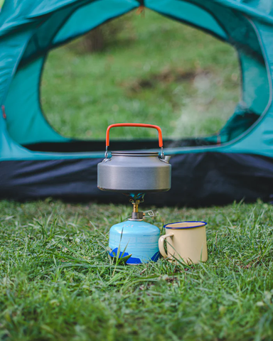 A flat tea kettle on top of a camping stove, with a tin cup beside it and a tent in the background