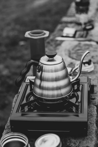 A black-and-white photo of a shiny steel tea kettle on top of a portable stove