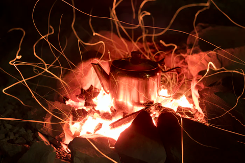 A medium-sized tea kettle placed directly on a campfire with glowing flames