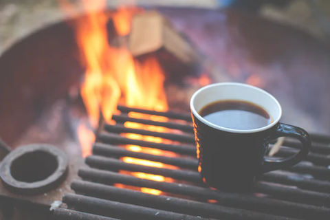 A cup of black tea next to a campfire