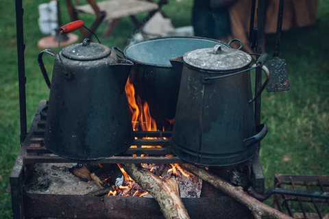 Two large tea kettles heating over a campfire