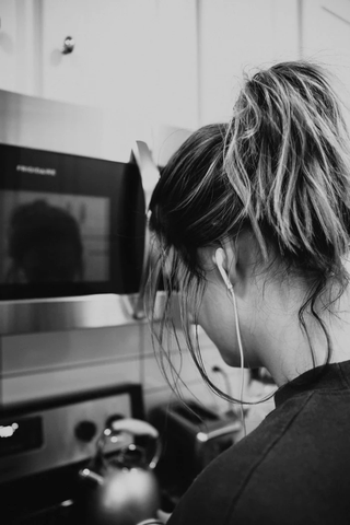 A woman wearing a ponytail is shown from behind. She is standing in front of a microwave, with a tea kettle sitting on the stove.