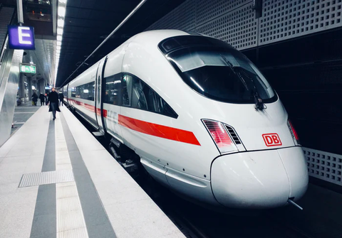 A sleek high-speed train. The train is clean and white with red stripes down the sides.