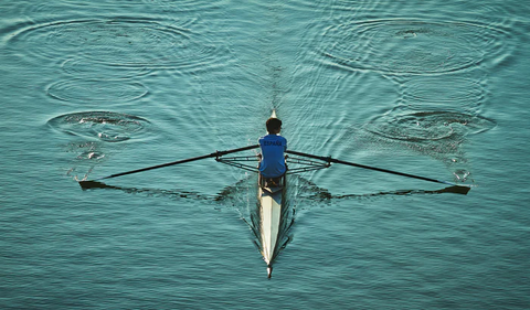A bird's-eye-view of a person rowing a boat.