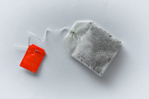 A tea bag with a red tag and a white background