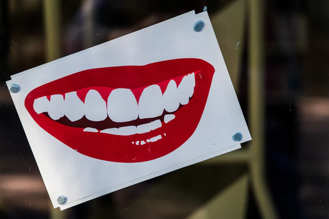 An illustration of a smiling mouth, with white teeth and red lipstick