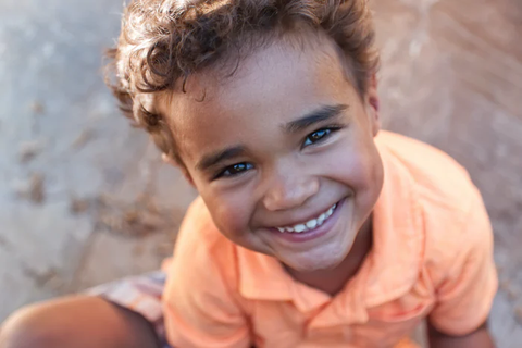 A small boy with curly hair and a big smile, wearing an orange t-shirt