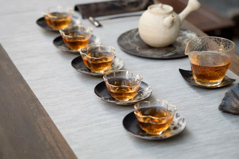 5 small glass cups and saucers lined up in a row on a white tablecloth. Each one is filled three quarters full with green tea. Behind them is a white teapot and a glass fairness cup halfway full of tea.