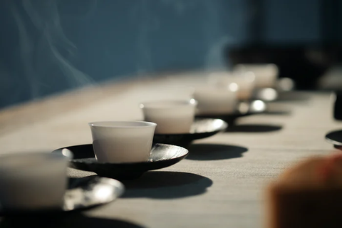 6 small white cups and saucers lined up in a row on a white tablecloth. Steam is rising from the cups. The focus is placed on the cups nearest the viewer.