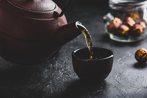Green tea from a cast iron teapot pouring into a black handle-less teacup. The teapot and teacup are setting on top of a black countertop with a jar of sweets in the background.